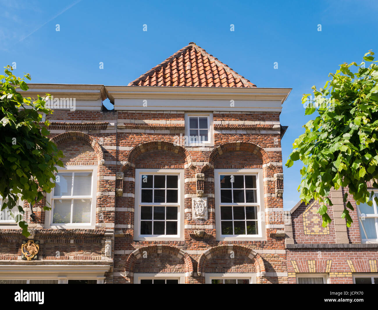 Front top facade of historic house  Hoogstraat 9 with cornice gable in old town of fortified city Woudrichem, Brabant, - Stock Image