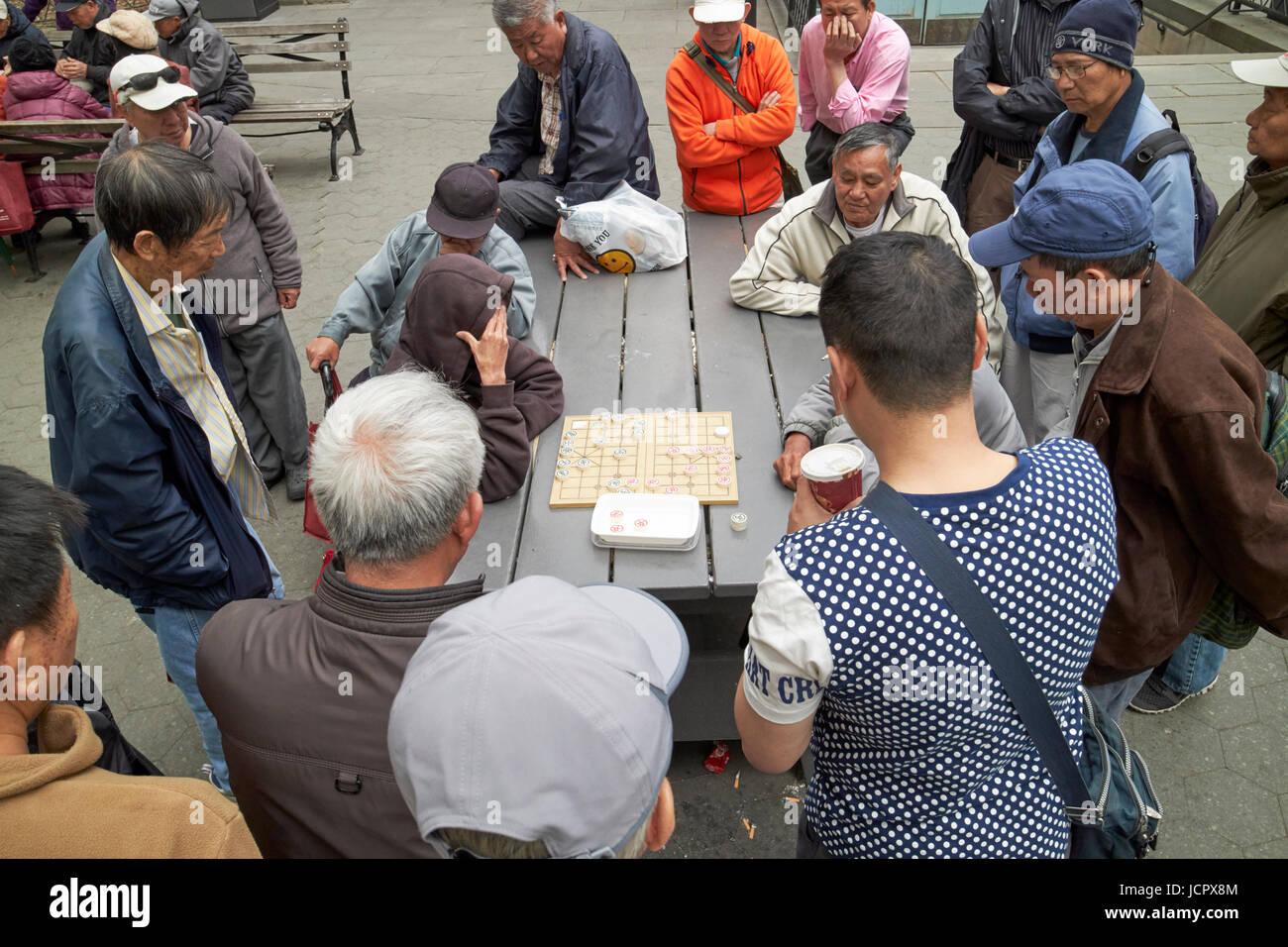crowd watching two men play xiangqi chinese chess in columbus park chinatown New York City USA - Stock Image
