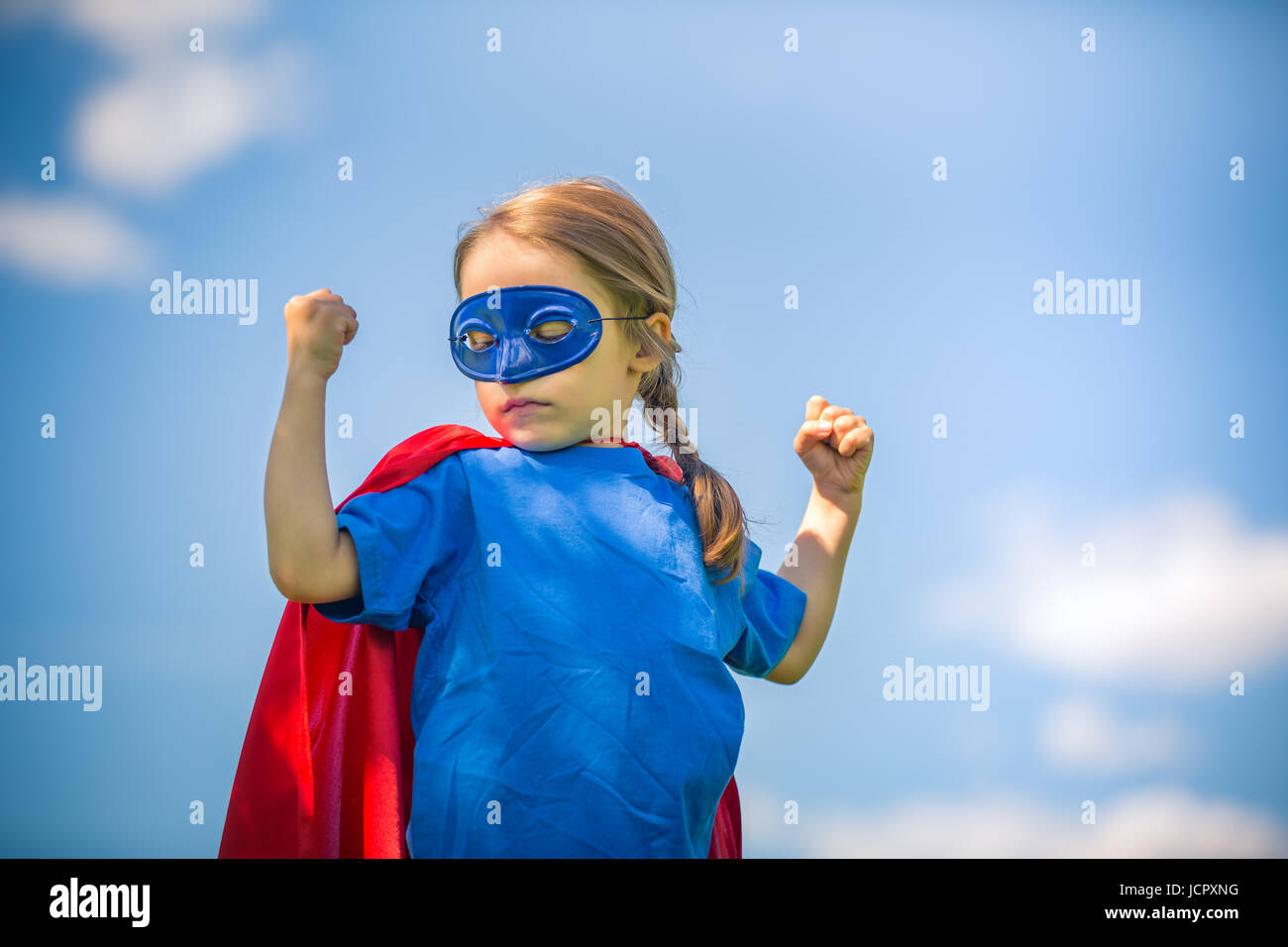 Funny little girl playing power super hero over blue sky background. Superhero concept. - Stock Image