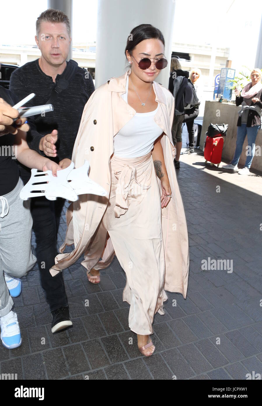 Demi Lovato wears a satin trench ensemble to the Los Angeles International Airport  Featuring: Demi Lovato Where: - Stock Image