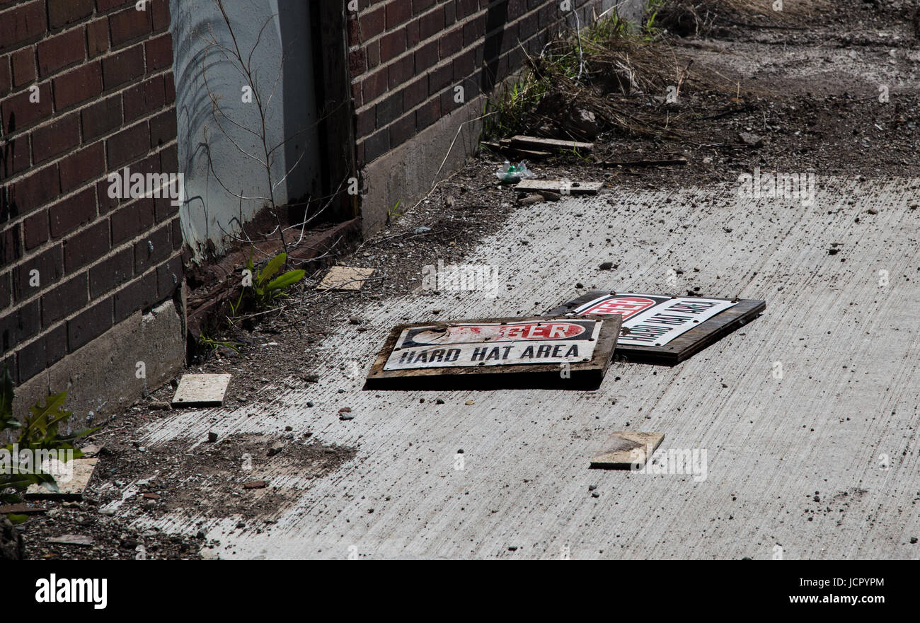 old Hard Hat Area signs among the debris of an old construction site - Stock Image
