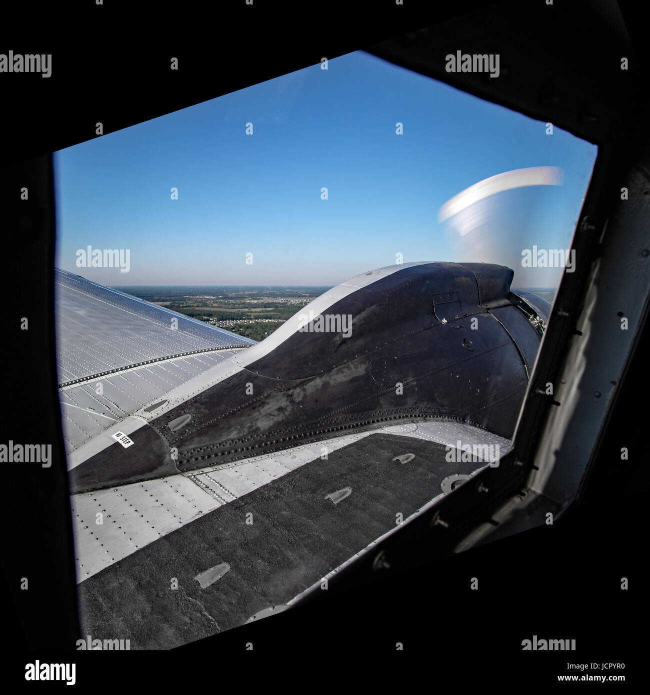 view of the sky, wing, and engine from  inside the airplane - Stock Image