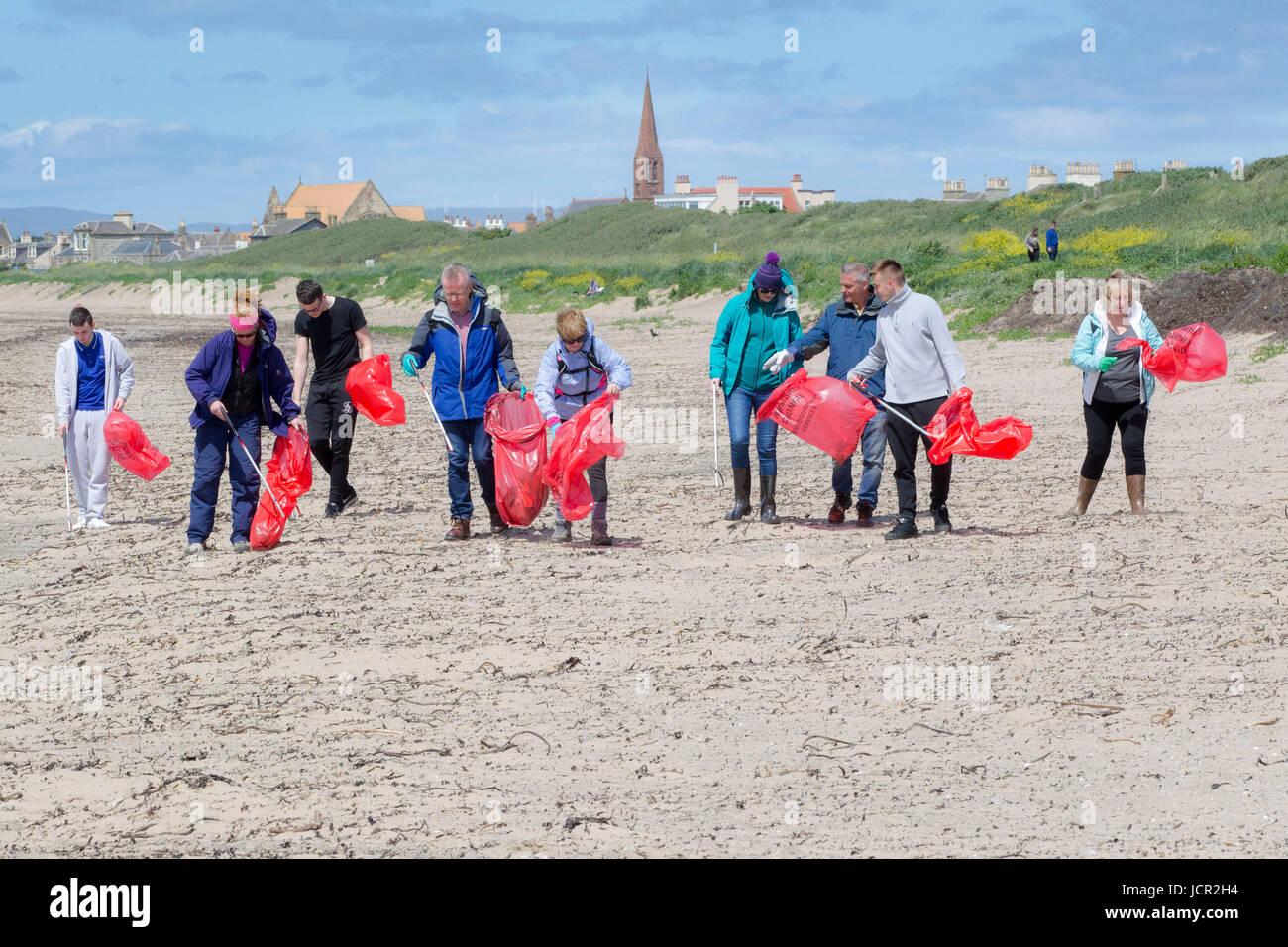 Volunteers picking up litter on Troon Beach Scotland - Stock Image