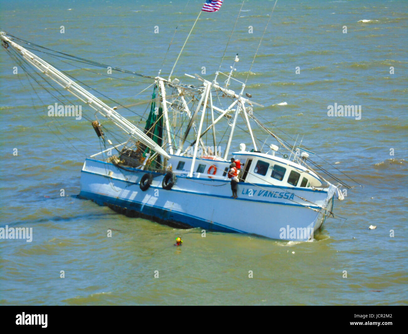 U.S. Coast Guard officers rescue three fishermen from the sinking 73-foot shrimp boat Lady Vanessa May 18, 2017 - Stock Image