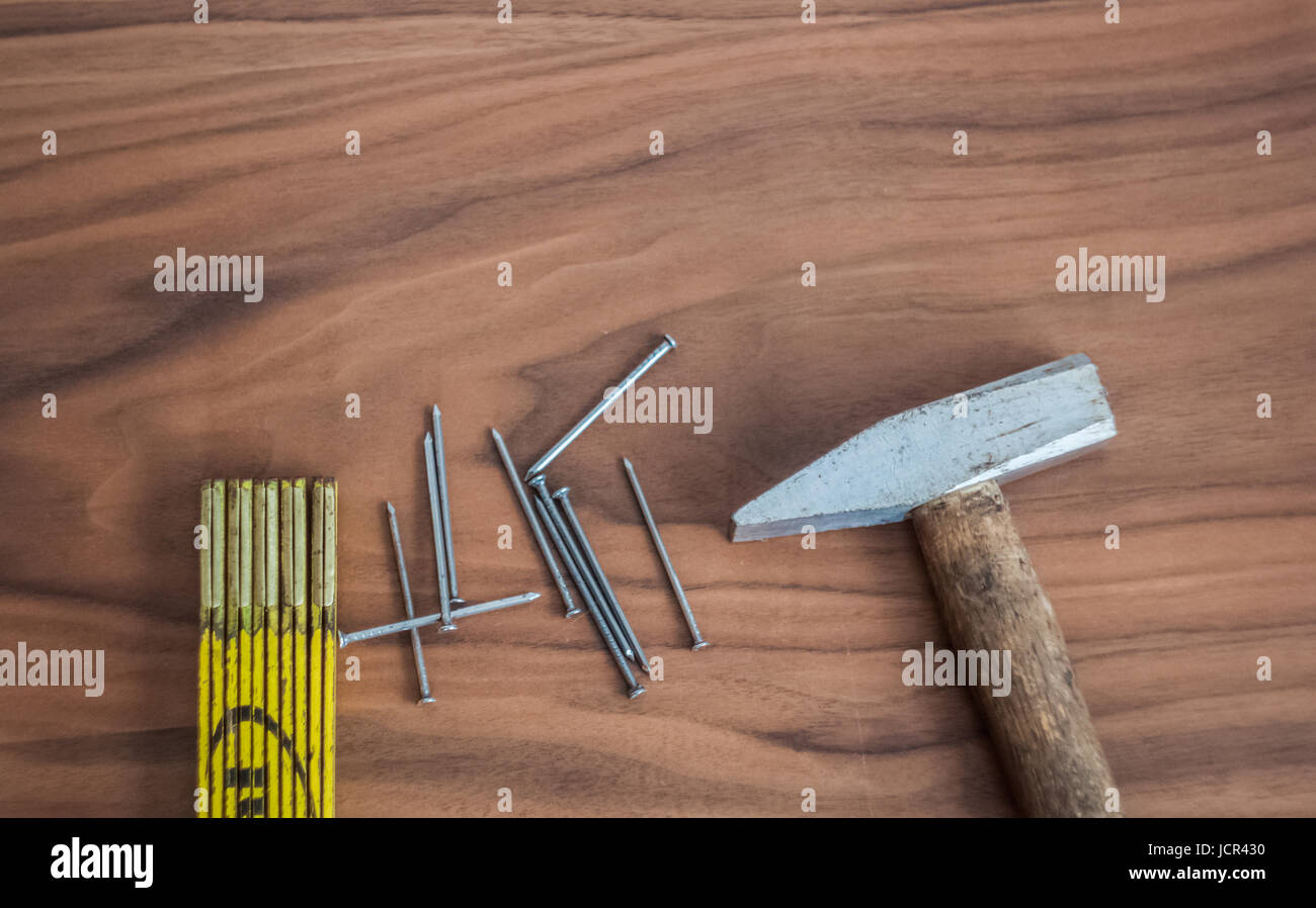 Hammer, nails and meter stick on a wooden table desk - Stock Image
