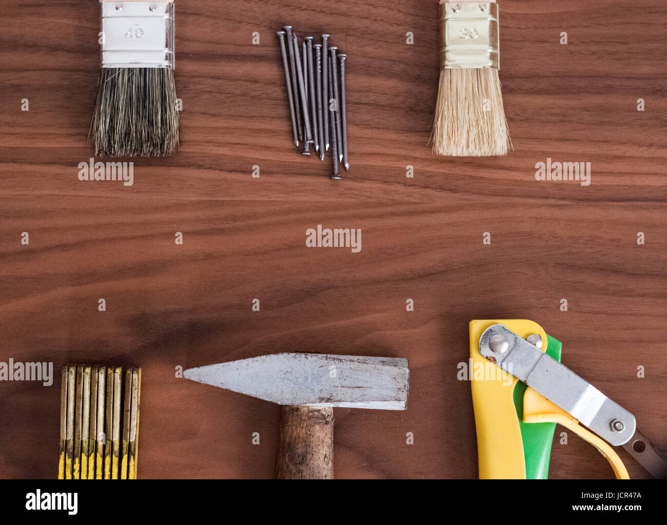 Hammer, nails, brushes, handsaw and meter stick on a wooden table desk - Stock Image