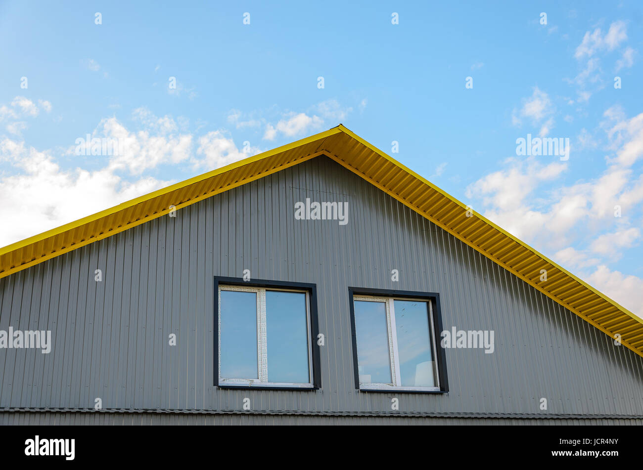 Corrugated metal facade. Pediment with two windows - Stock Image