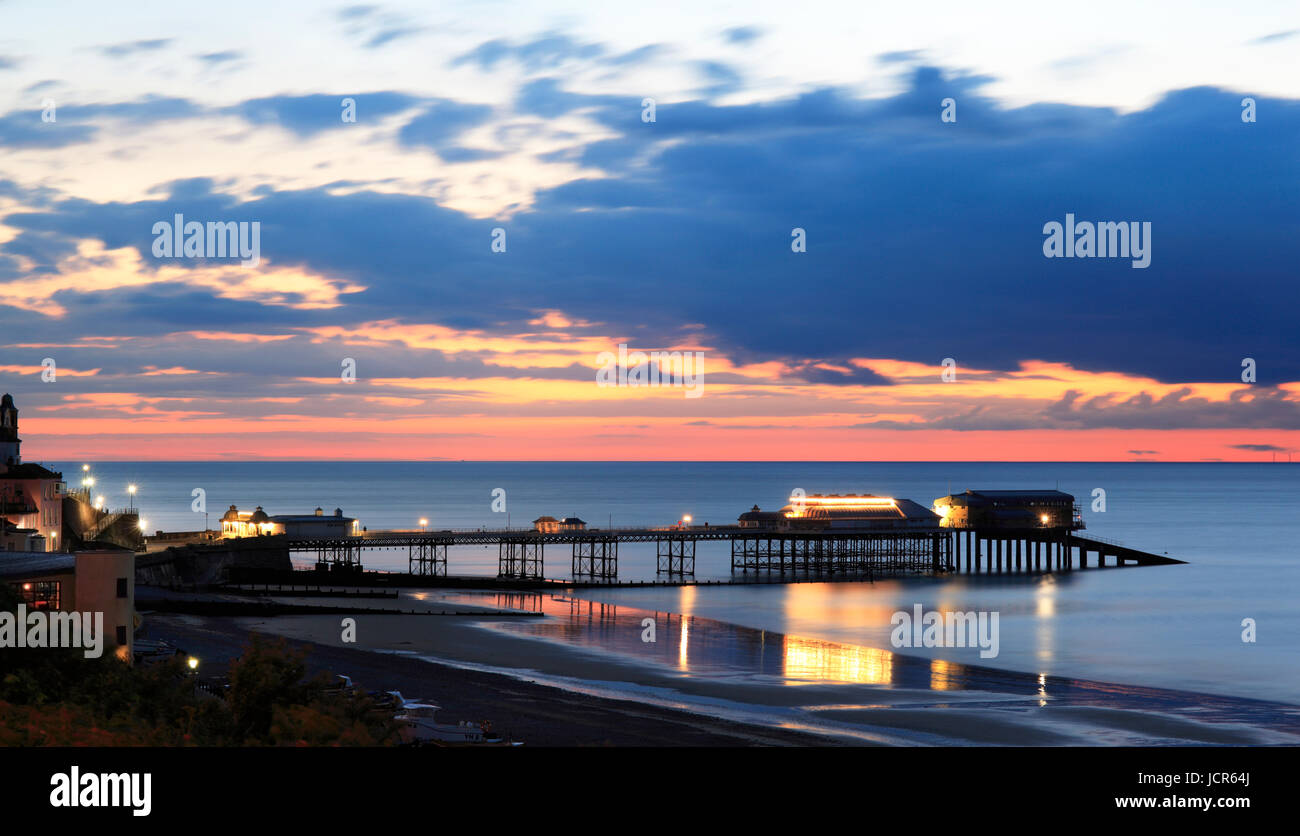 The pier illuminted at night as dusk descends over the North Sea, Cromer, North Norfolk, England, Europe - Stock Image