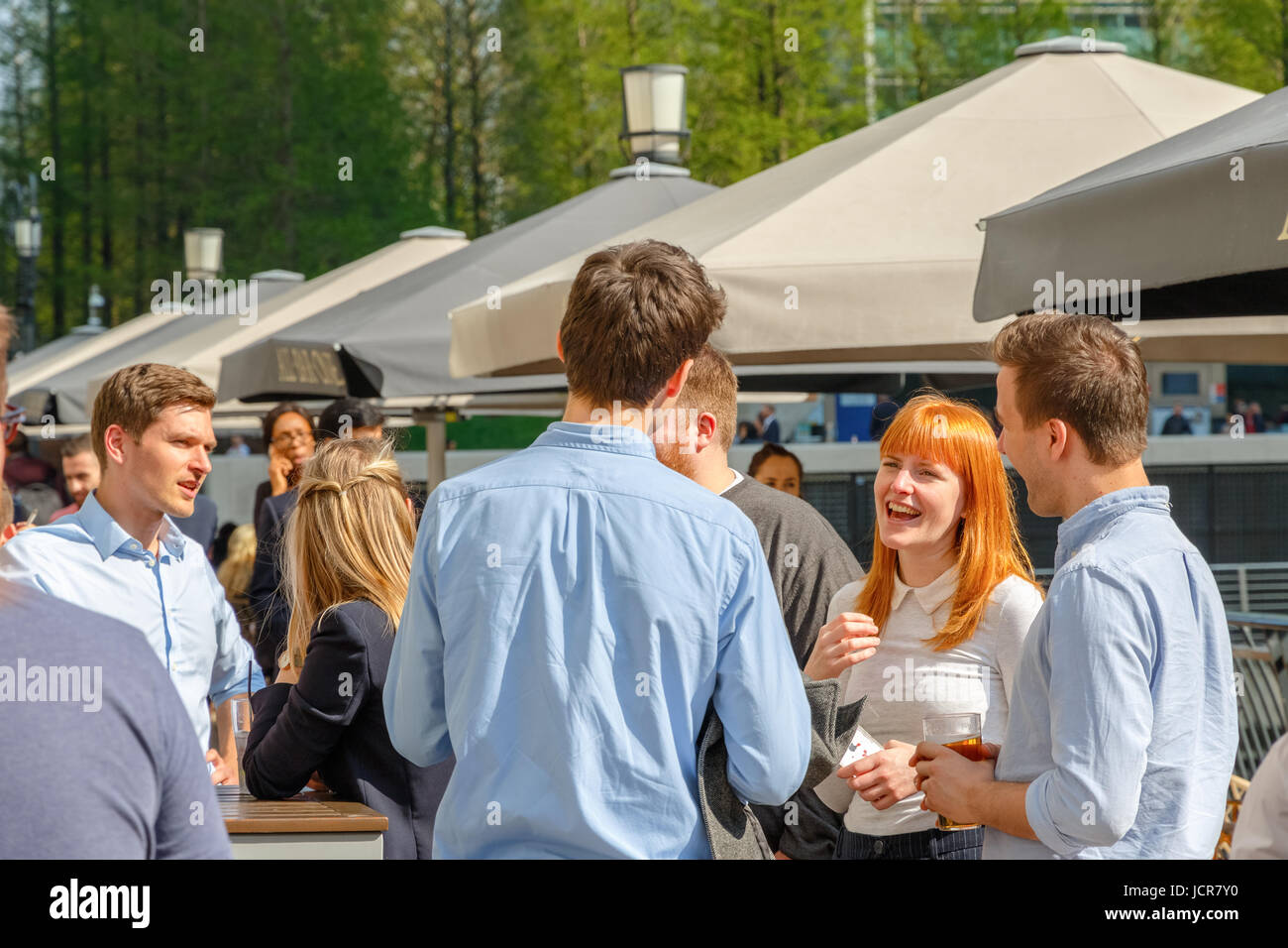 London, UK - May 10, 2017 - A young businesswoman drinking with her colleagues at a packed outdoor bar in Canary - Stock Image