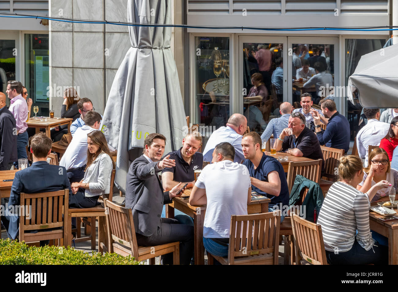 London, UK - May 10, 2017 - An outdoor bar in Canary Wharf packed with people drinking and chatting business on - Stock Image
