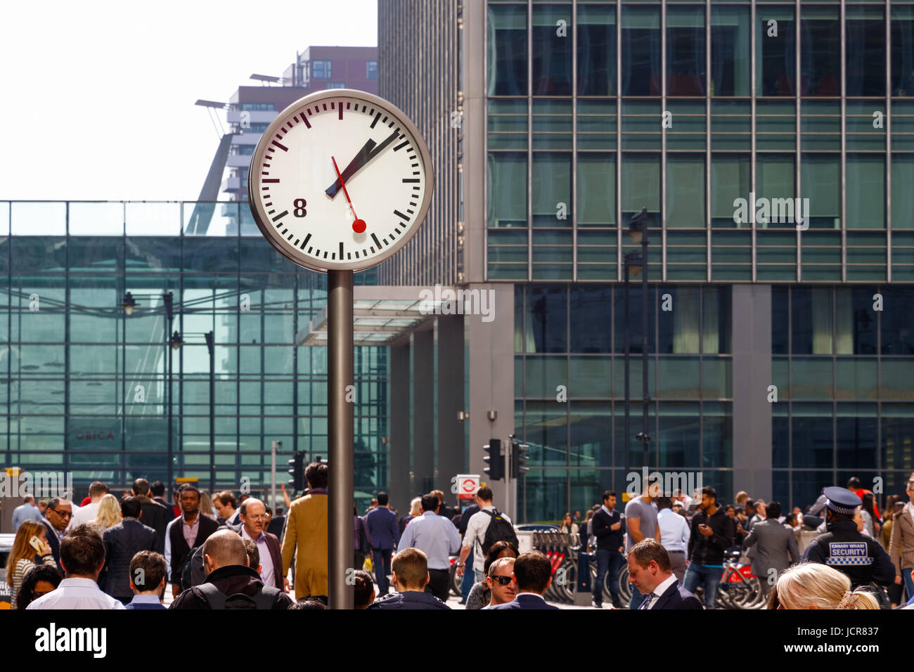 London, UK - May 10, 2017 - A public clock in Reuters Plaza, Canary Wharf packed with people walking through Stock Photo