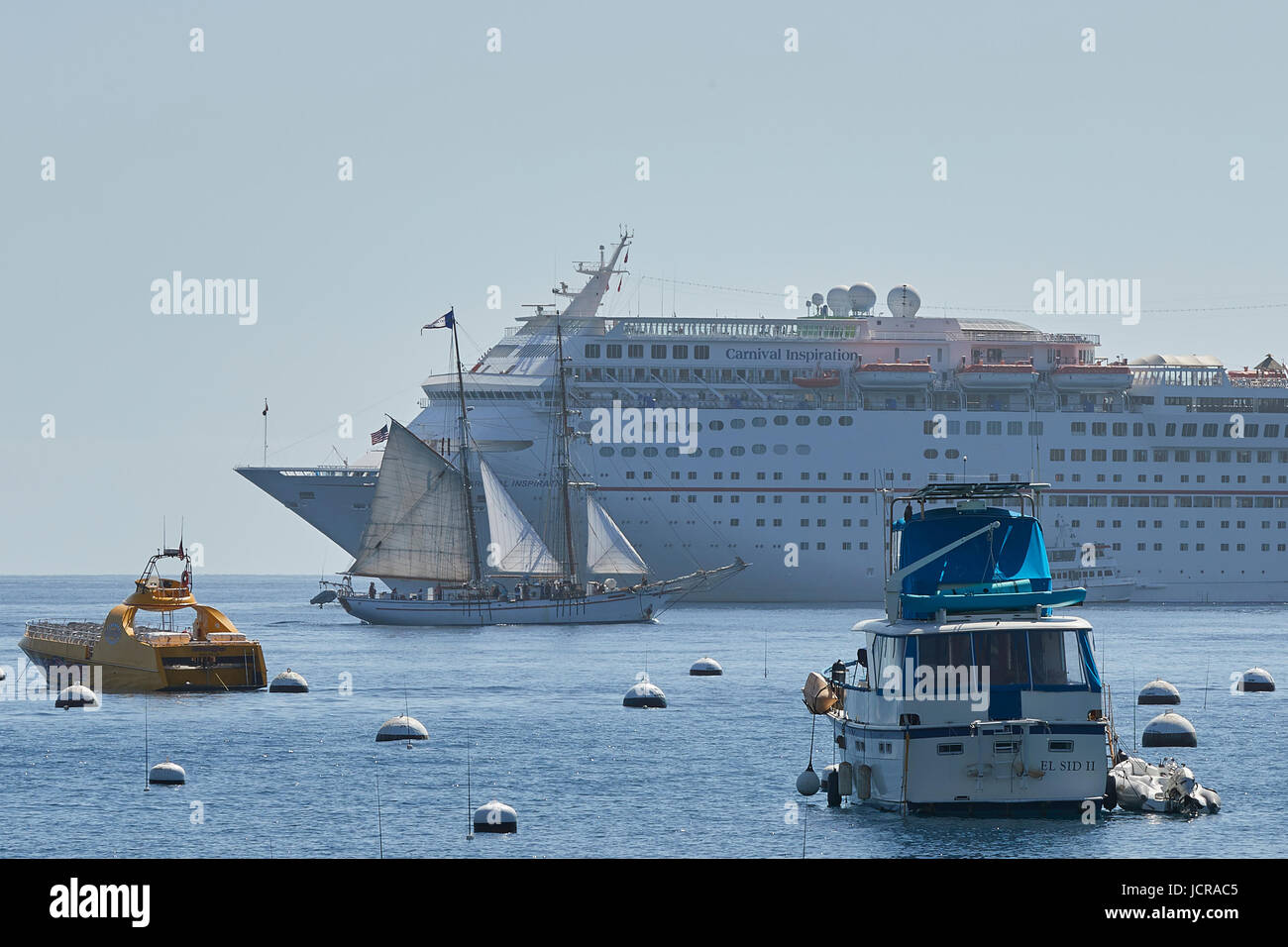 square rigged tall ship under sail passes the cruise liner