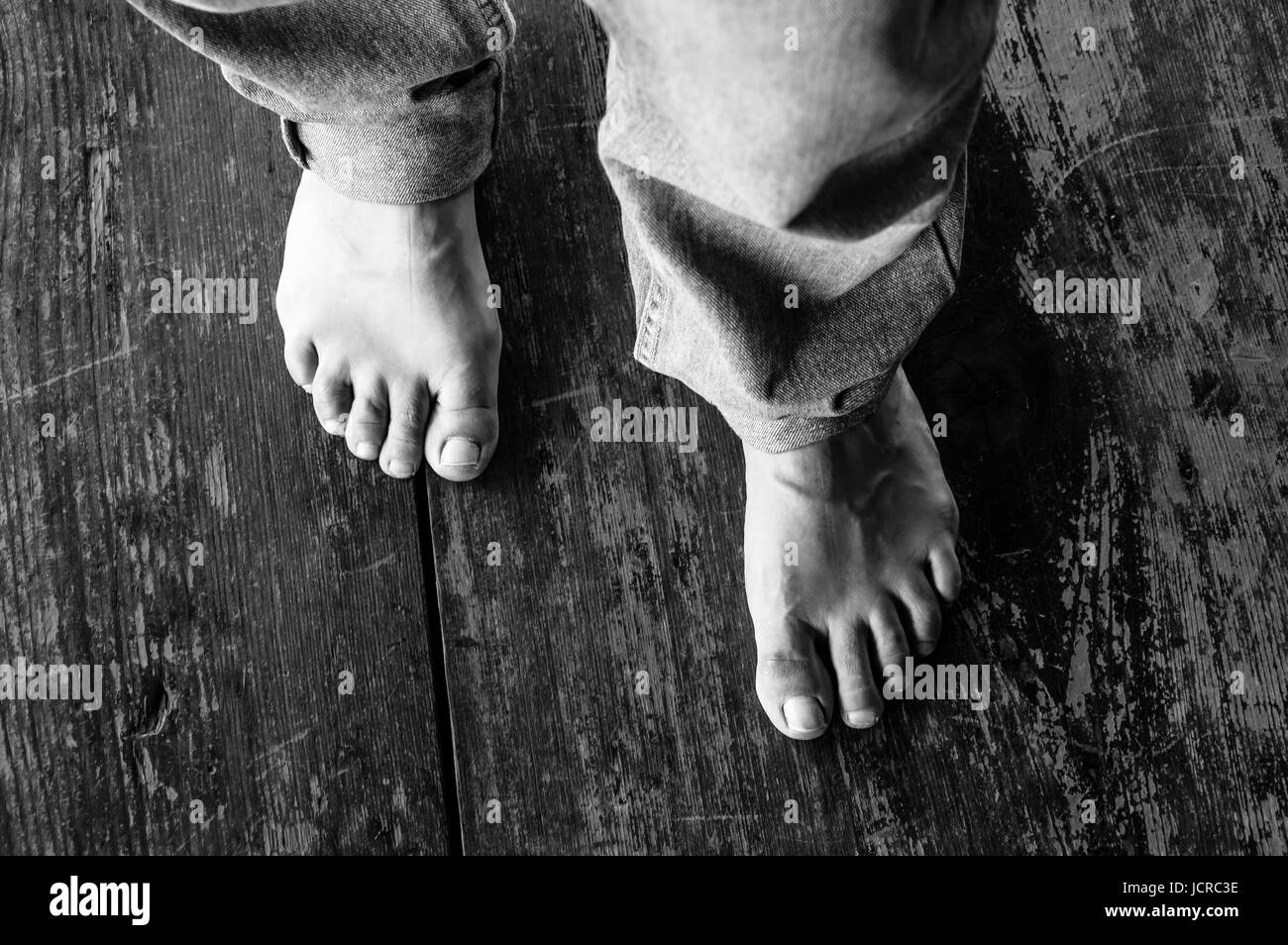 Close Up of Woman Bare Feet on Wooden Floor - Stock Image