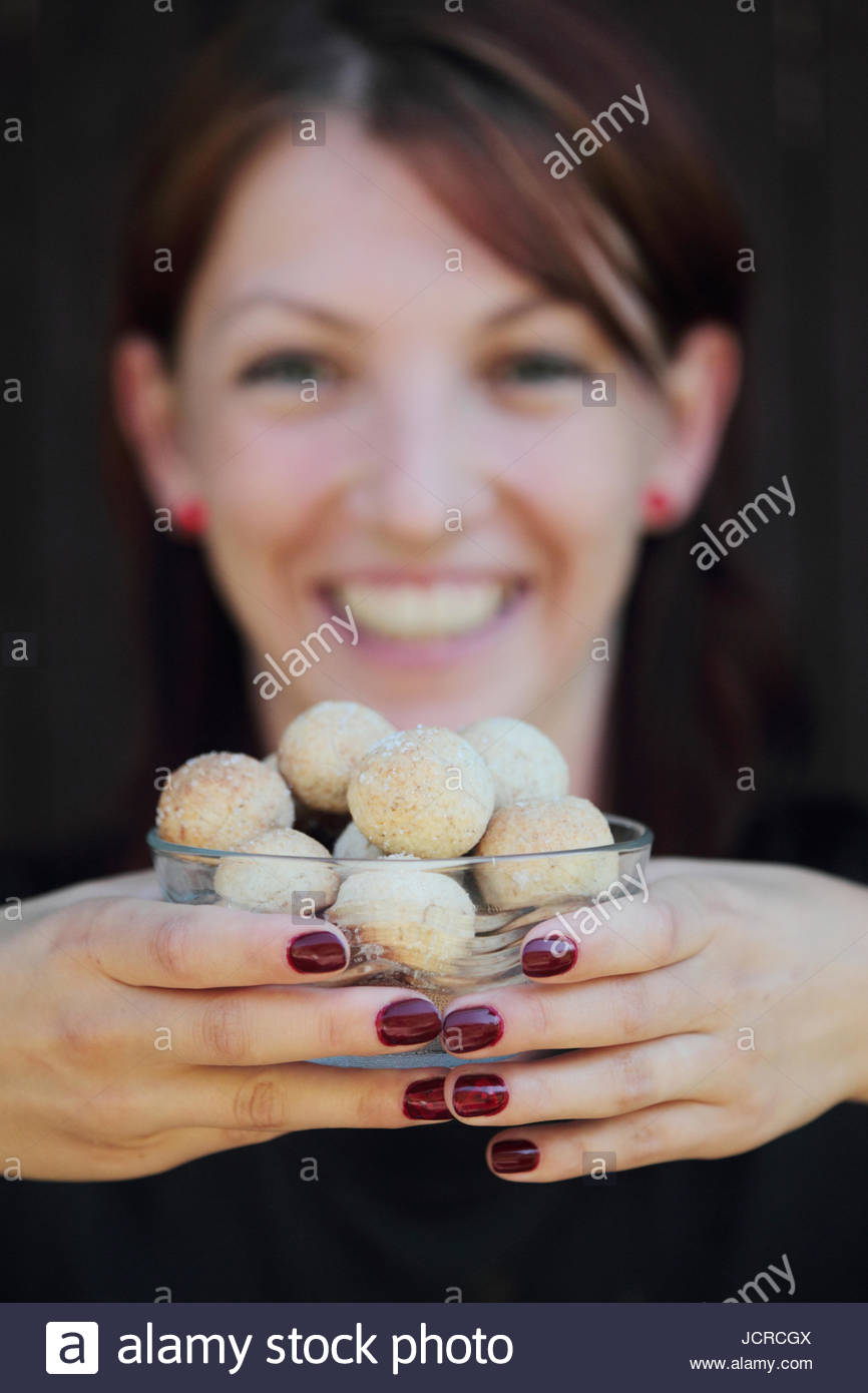 A woman with diabetes mellitus type 1 holds out a dish of delicious, and safe, treats she created for sufferers - Stock Image