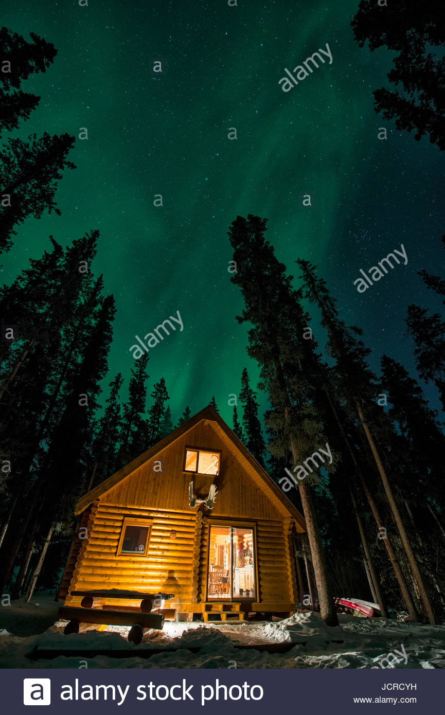 Norther Lights  Aurora Images  in winter in Canada's far north  Aurora Borealis over a log cabin within a boreal - Stock Image