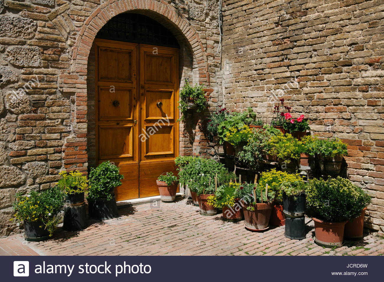 Potted plants by a closed door in San Gimignano. - Stock Image