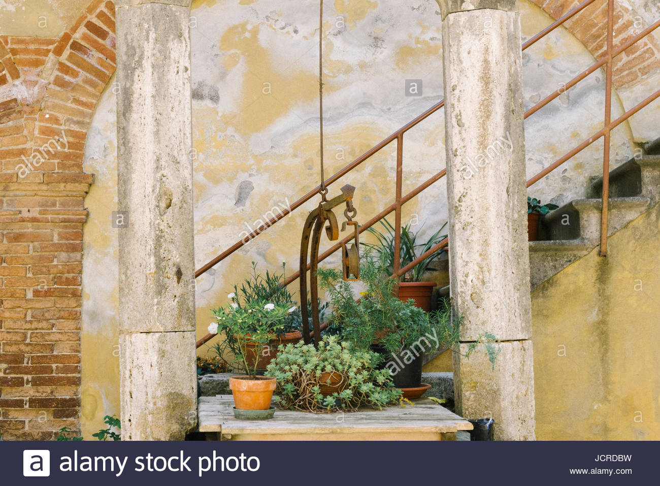 Potted plants next to stairs in San Quirico D'Orcia. - Stock Image