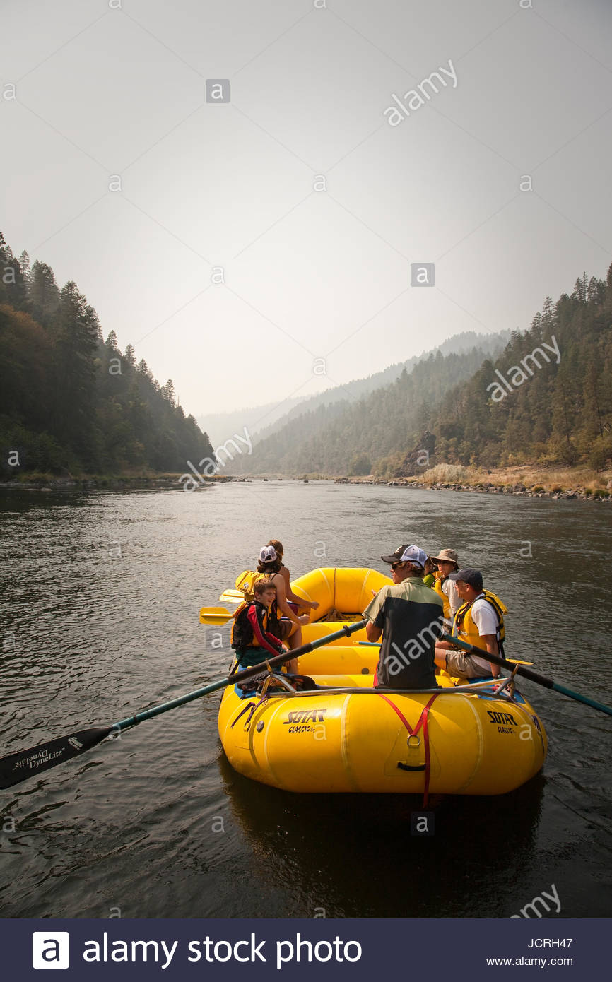 A raft full of paddlers heads down a flat stretch of the Rogue River on a hazy afternoon. Editorial Use Only. - Stock Image