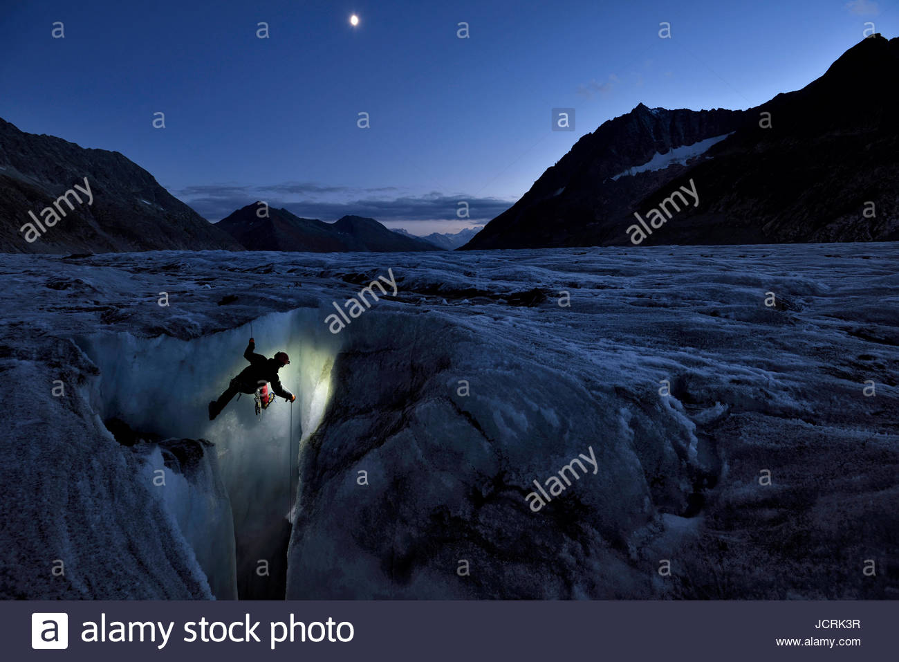 In the early evening light, an Italian cave explorer begins his descent down a moulin on the Aletschgletscher when - Stock Image