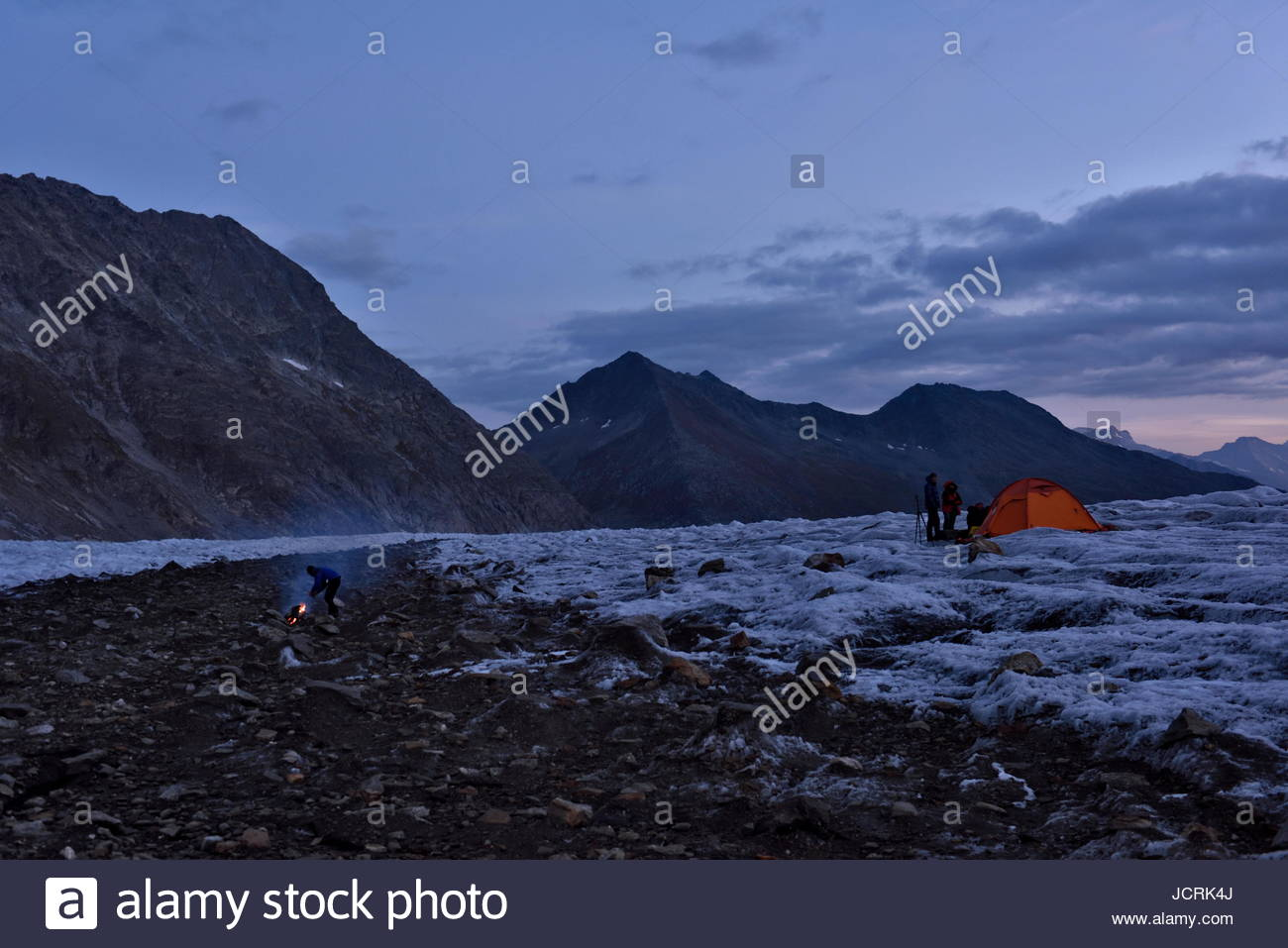 The team of Italian cave explorers settle into the evening at their base camp on the Aletschgletscher. Warm twilight - Stock Image