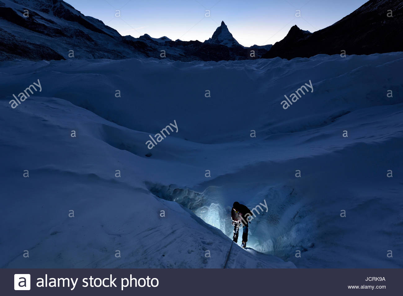 British cave explorer and glaciologist Sam Doyle emerges from a moulin in the early evening with the Matterhorn - Stock Image