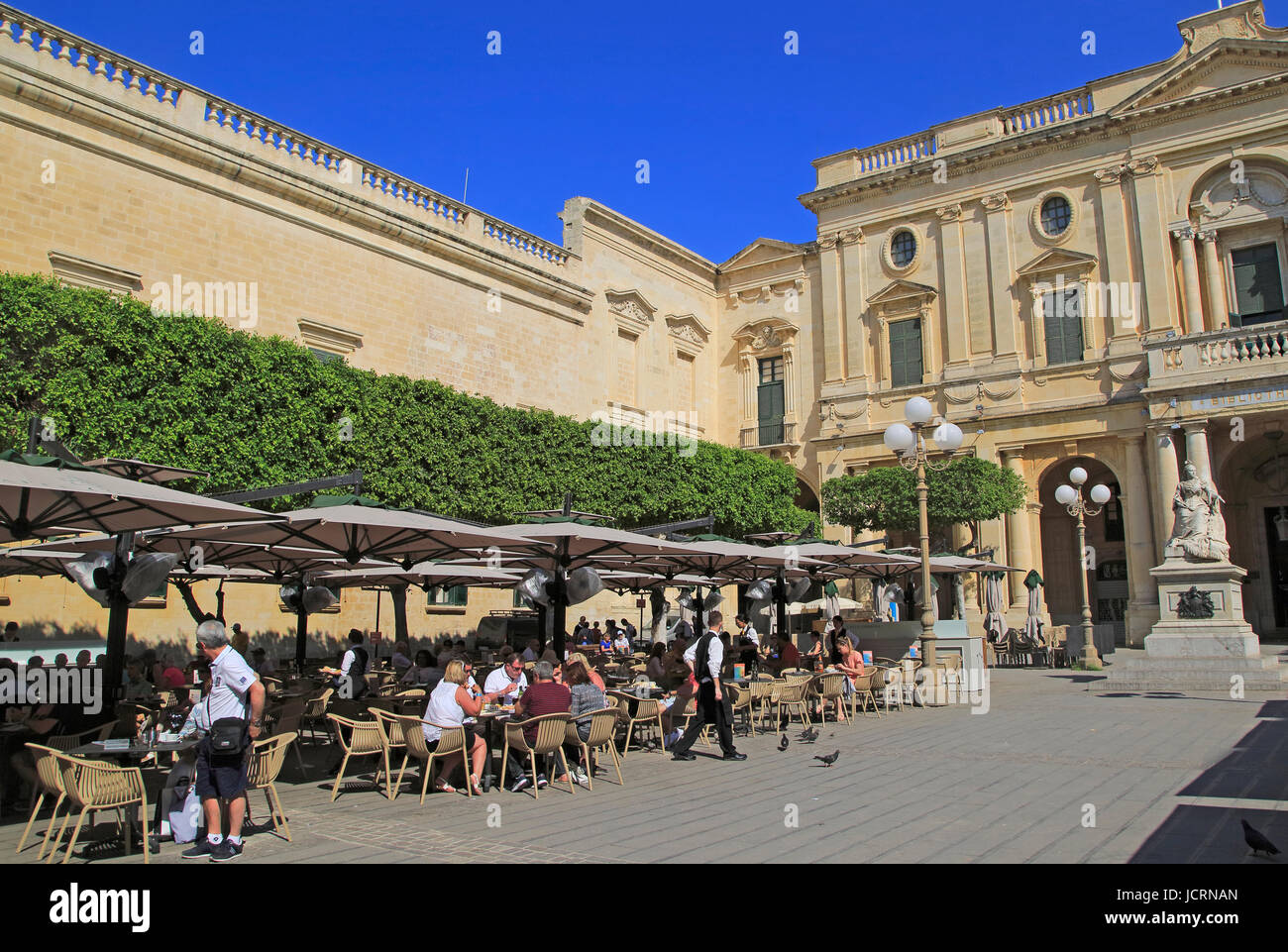People at cafe tables next to National Library building, Republic Square, Valletta, Malta - Stock Image