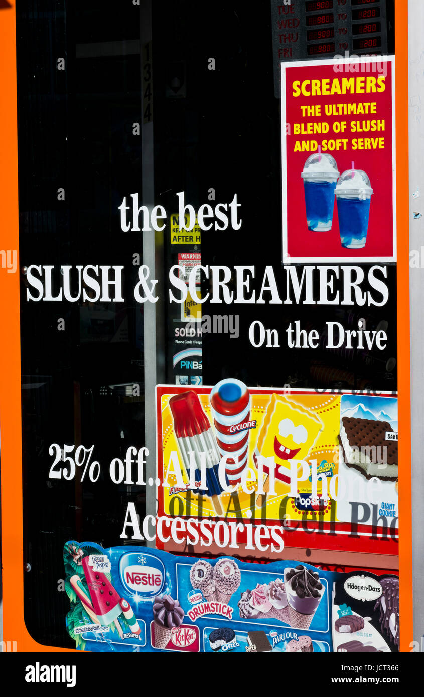 Storefront window on Commercial Drive, Vancouver, advertising the best Slush and Screamers. - Stock Image