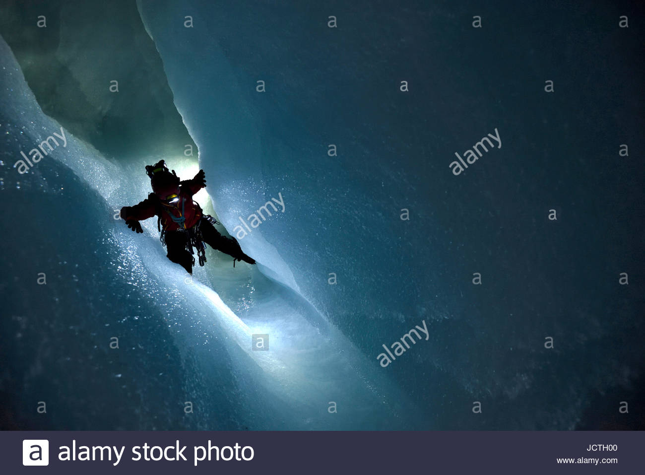 British cave explorer Josh Bratchley traverses around a pool of ice cold water in a narrow ection of passage-way - Stock Image