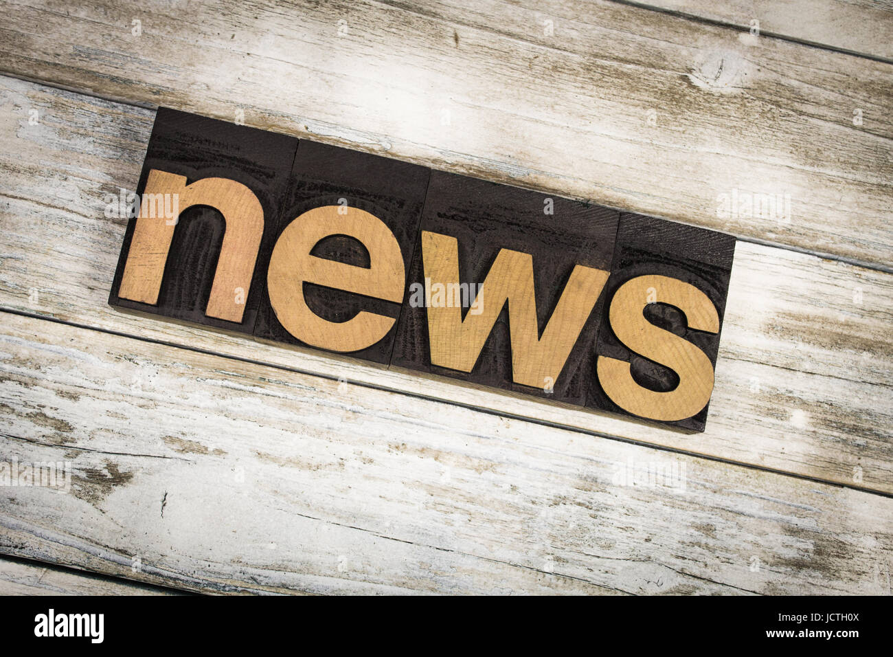 The word 'news' written in wooden letterpress type on a white washed old wooden boards background. - Stock Image