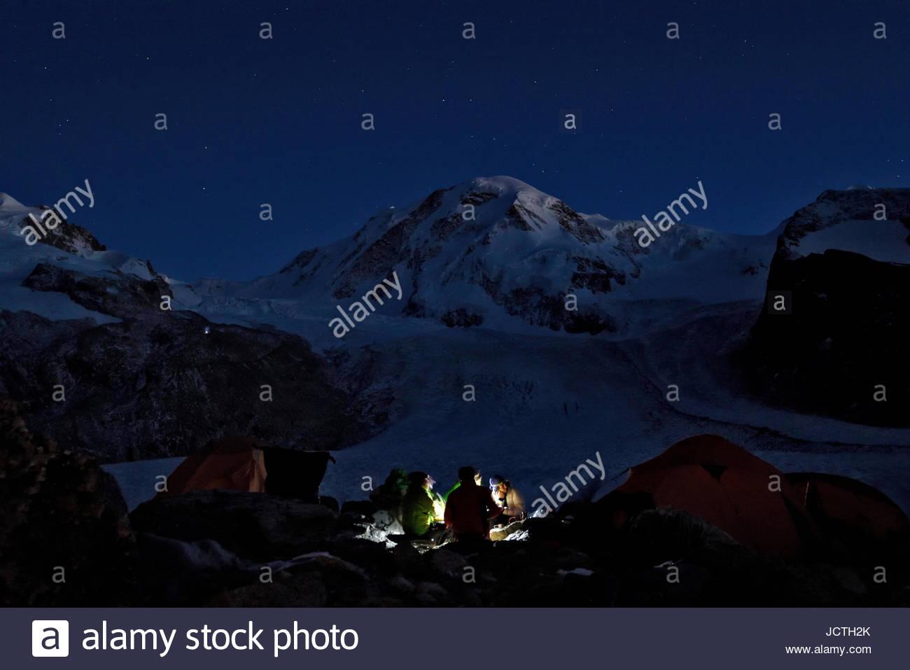 Four Italian cave explorers enjoy their last night on the glacier beneath the stars eating their meal. The faint - Stock Image