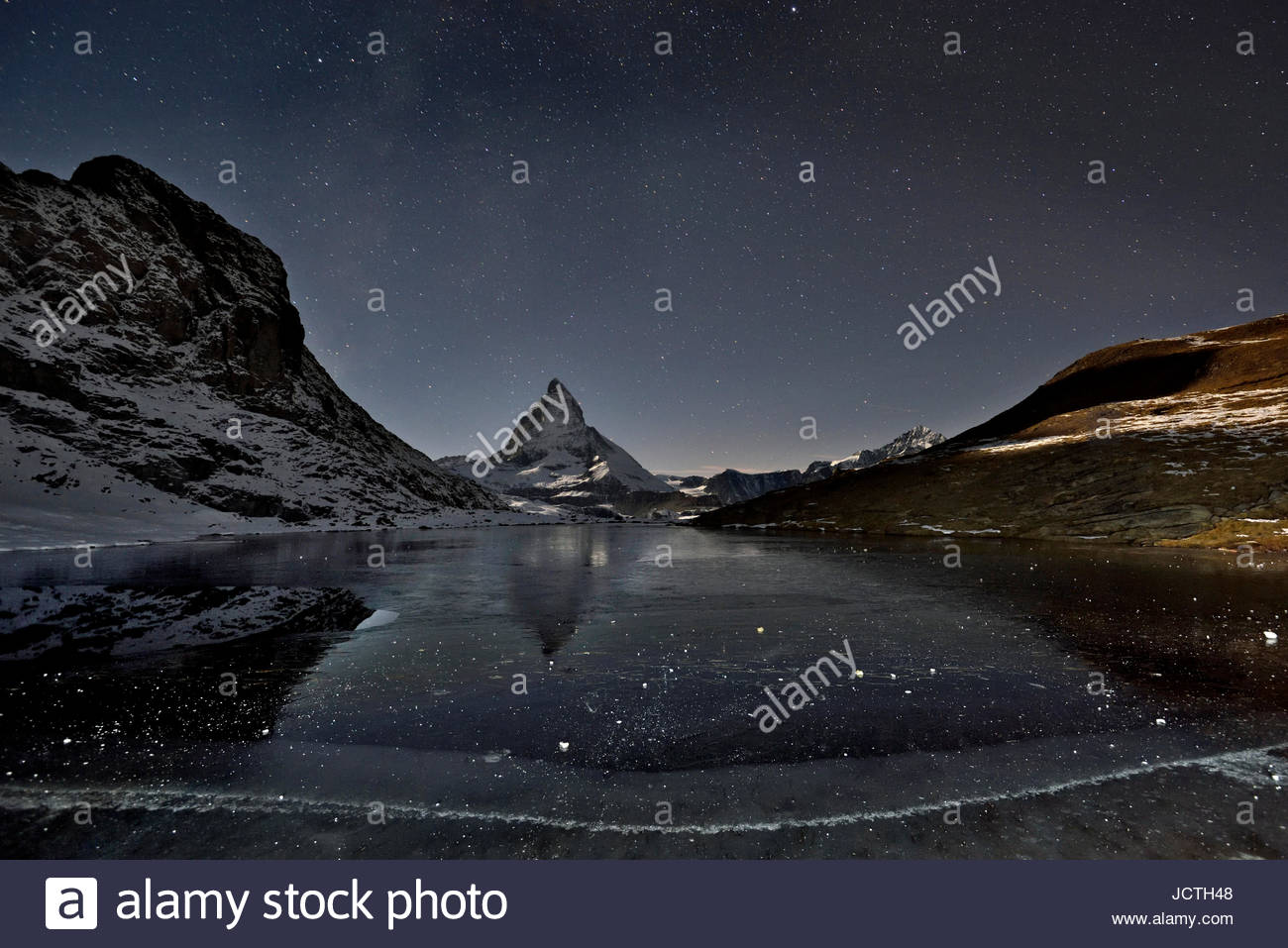 In the evening the Matterhorn (mountain) dominates the skyline. Stars shine bright in the night sky and a frozen - Stock Image