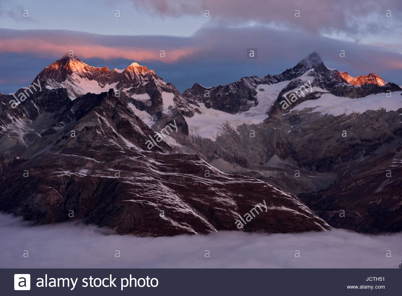 Sunrise over the neighbouring mountains east of the majestic Matterhorn (out of shot). - Stock Image