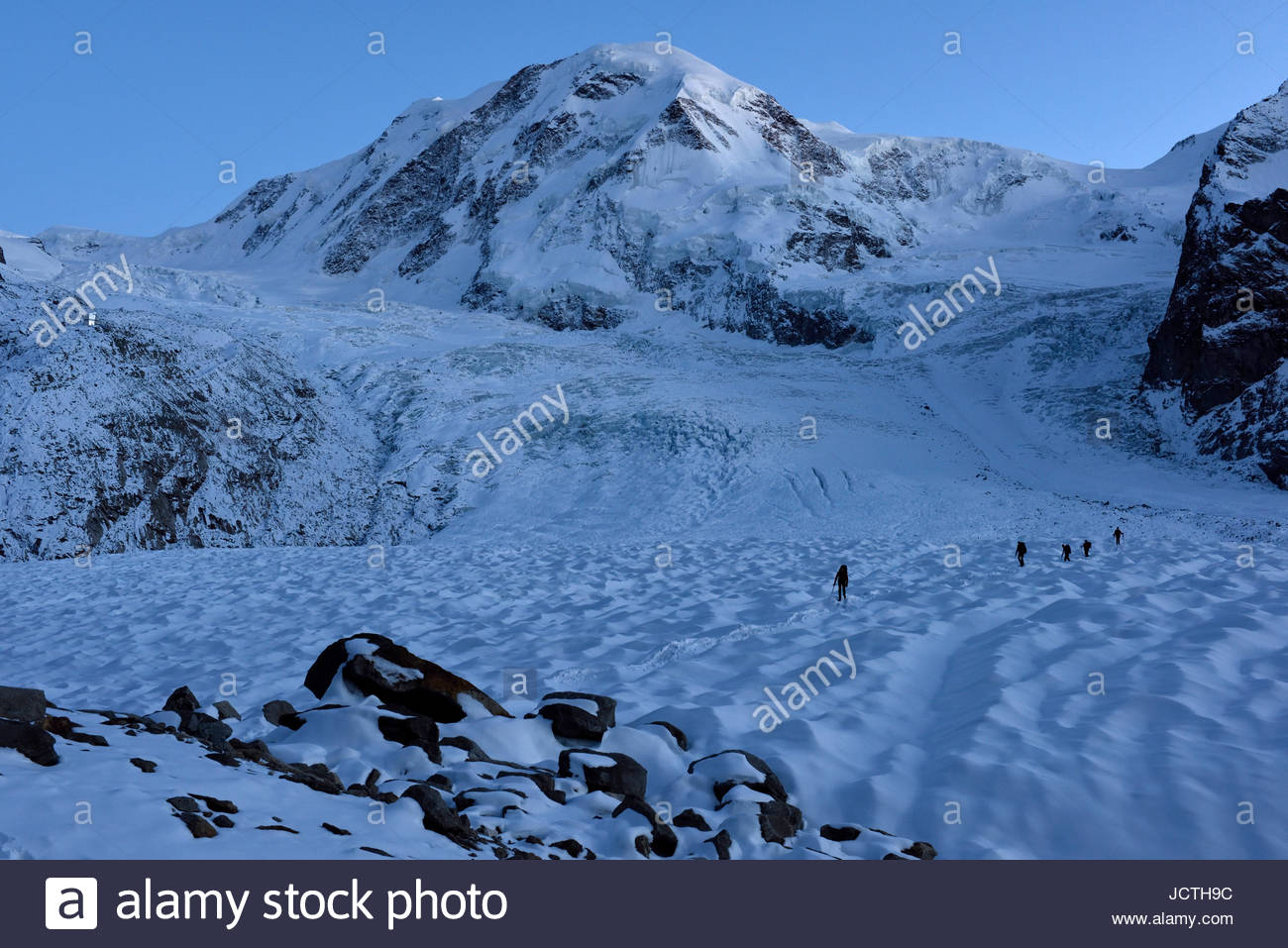 Four members of the group of Italian cave explorers return from a long day out on the ice exploring moulins in the - Stock Image