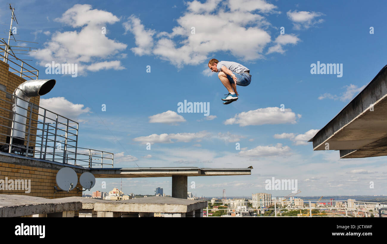 A man is jumping from roof to roof. Parkour. Active lifestyle. Roofer - Stock Image