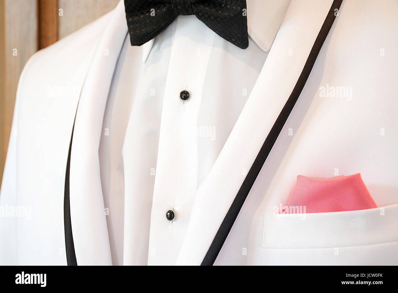 de6fe3caf434a white tuxedo jacket with black bow tie and pink handkerchief in pocket -  Stock Image