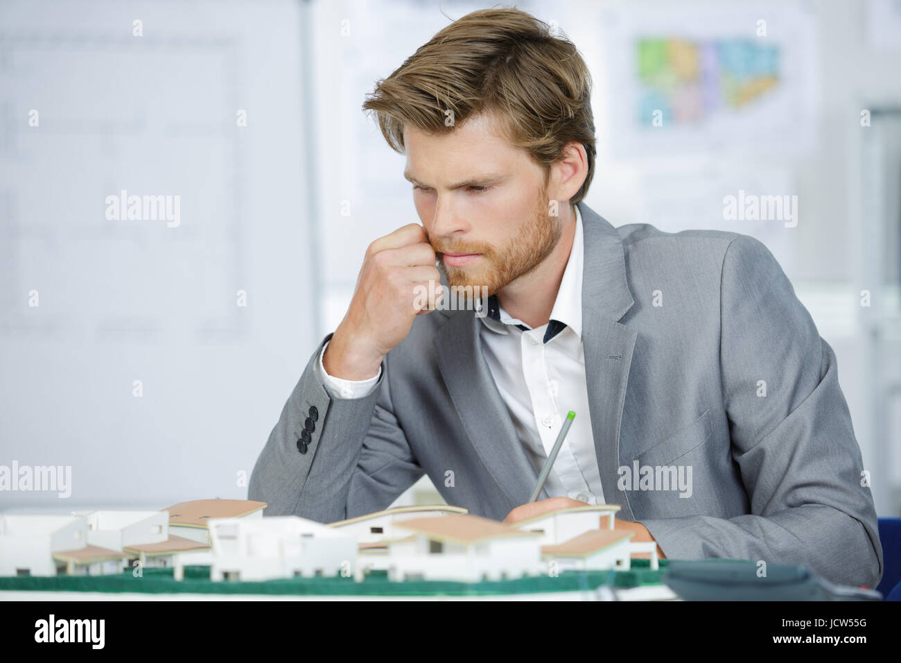 male architect looking at house models - Stock Image