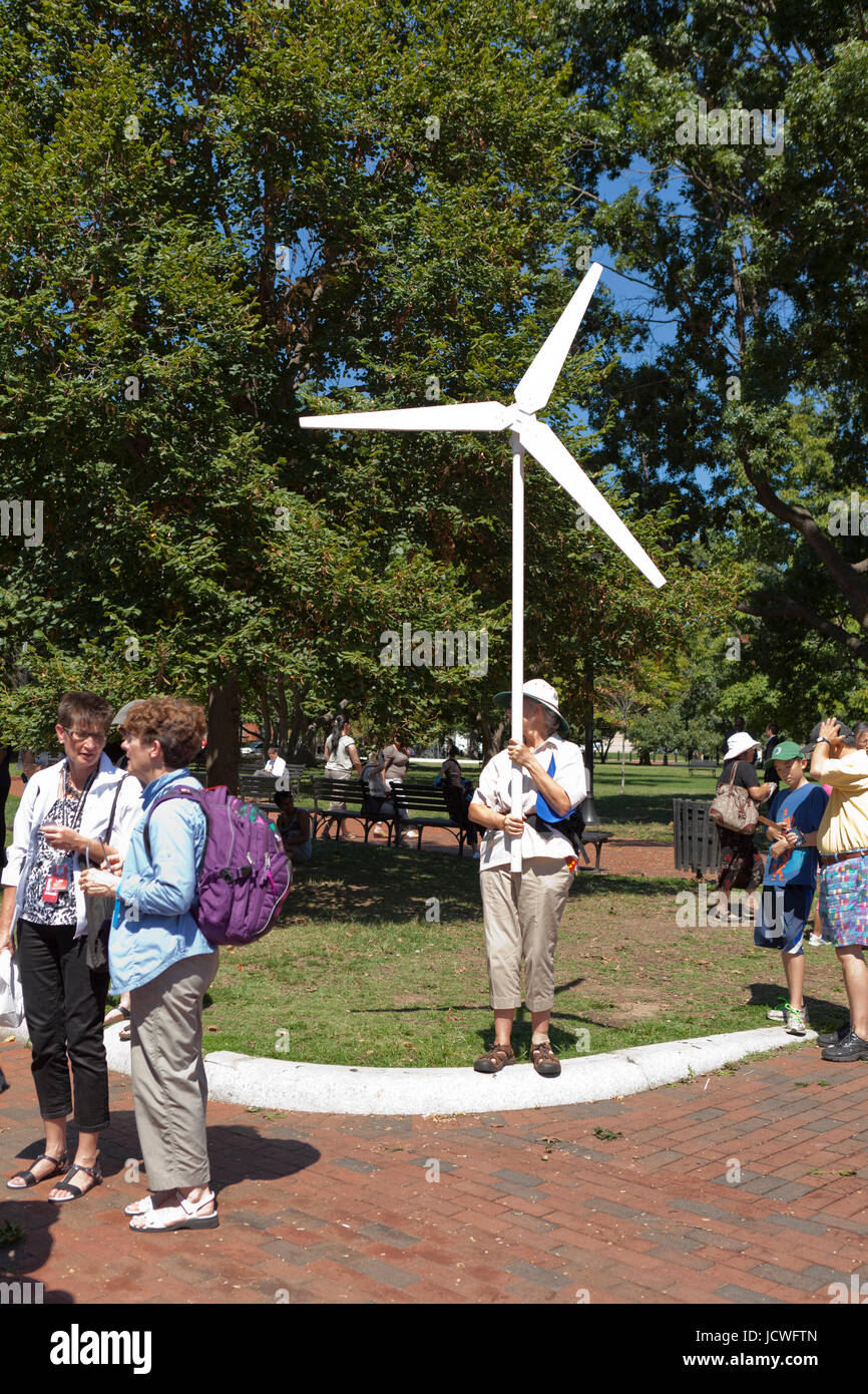 Environmental activist holds up a wind turbine model, in support of wind and renewable energy, during a climate - Stock Image
