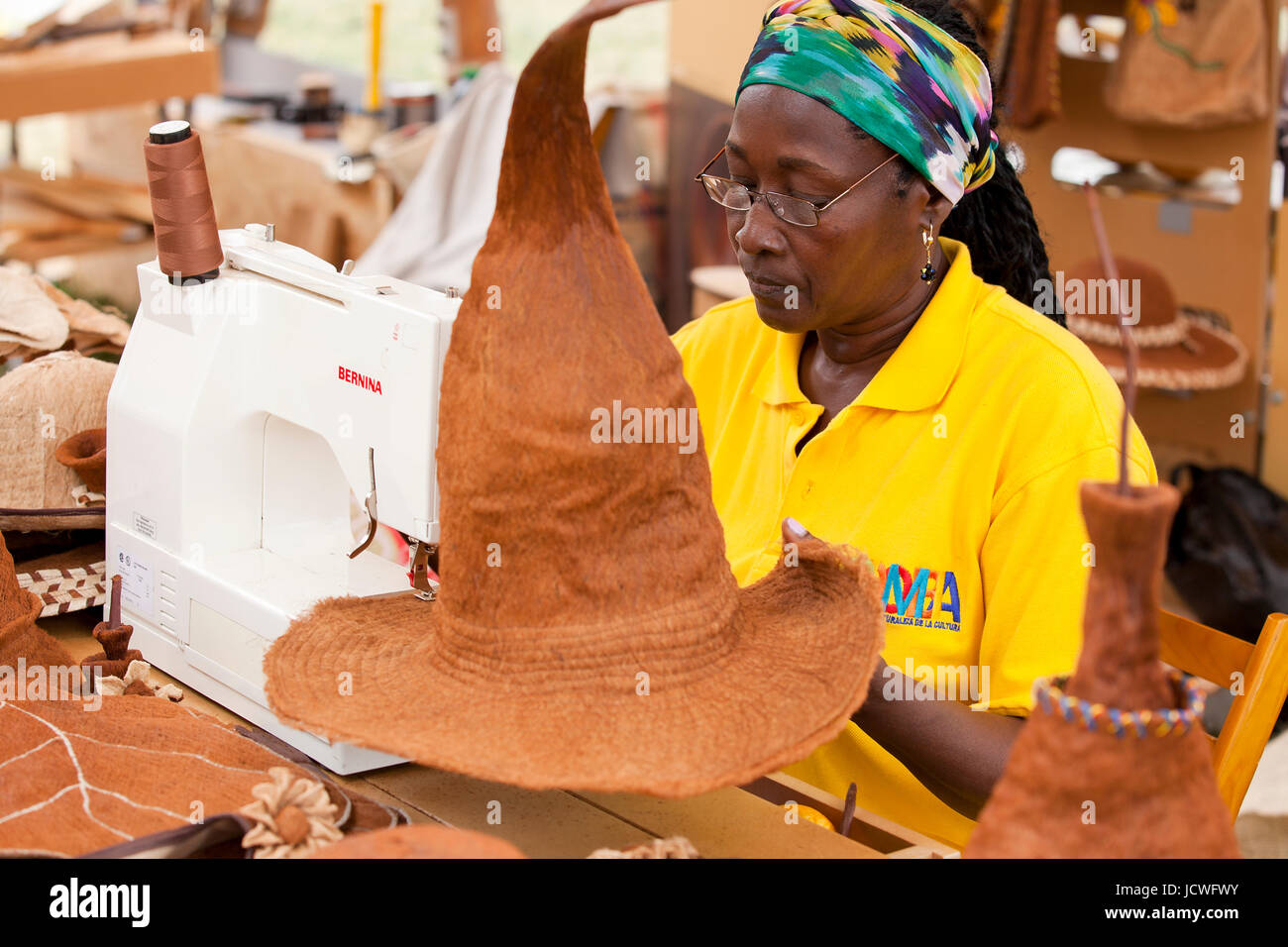Afro-Colombian woman hat maker working with a sewing machine, using coconut fiber (coir) - USA - Stock Image