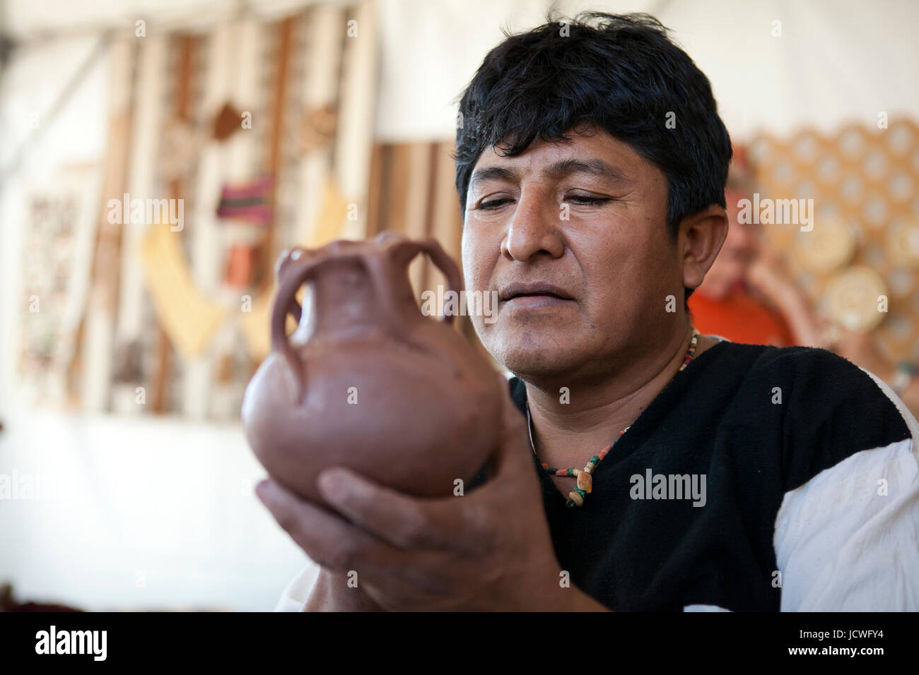 Indigenous Colombian pottery maker holding clay pot - Stock Image