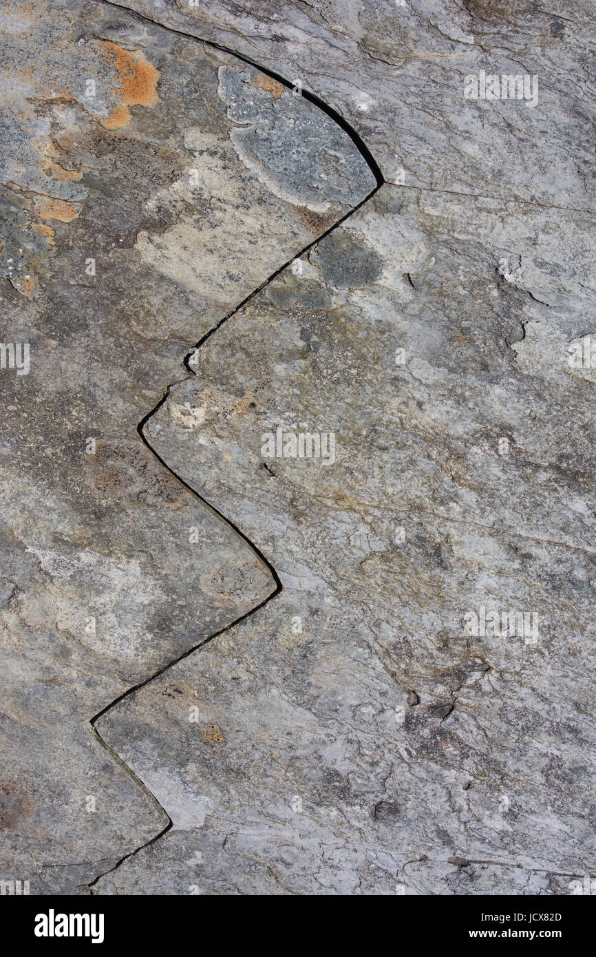 Rock texture with lichen and zig zag crack for backgrounds and textures. Zig zag crack resembles a graph plotting. - Stock Image