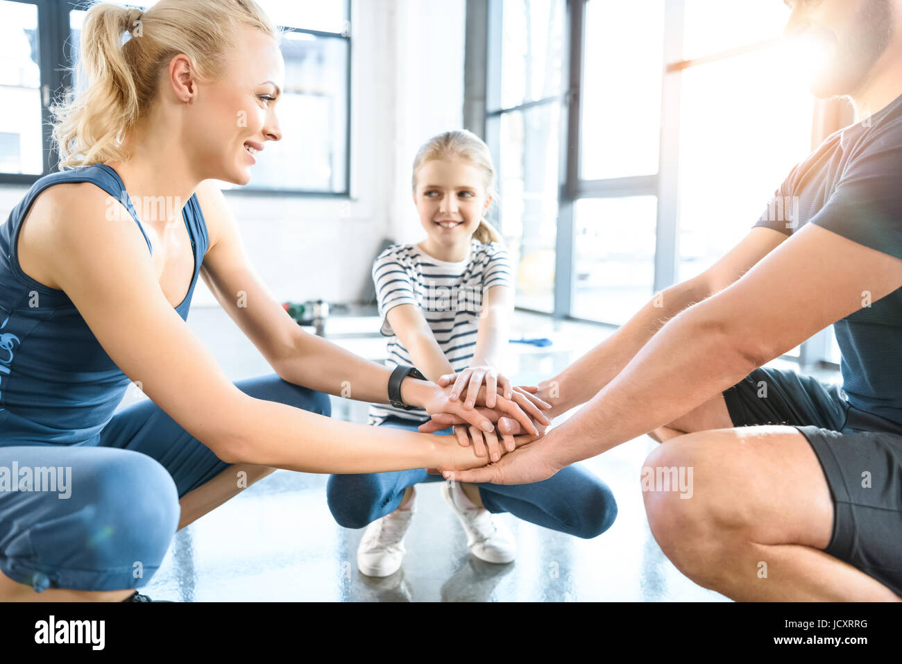 Family holding hands together at fitness center - Stock Image
