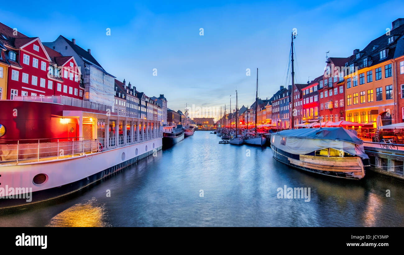 Nyhavn with its picturesque harbor with old sailing ships and colorful facades of old houses in Copenhagen, Denmark. - Stock Image