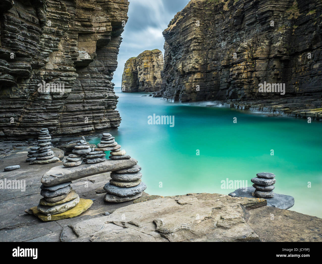 Cairns formed from stacks of pebbles beside turquoise seawater in a natural harbour below Sinclair Girnigoe Castle Stock Photo