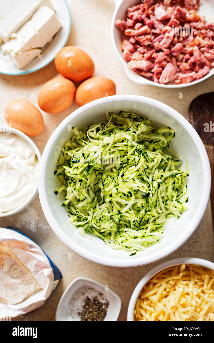 Courgette cake (frittata) ingredients mixed in white bowl - eggs, flour, grated courgette, bacon, feta, mascarpone - Stock Image