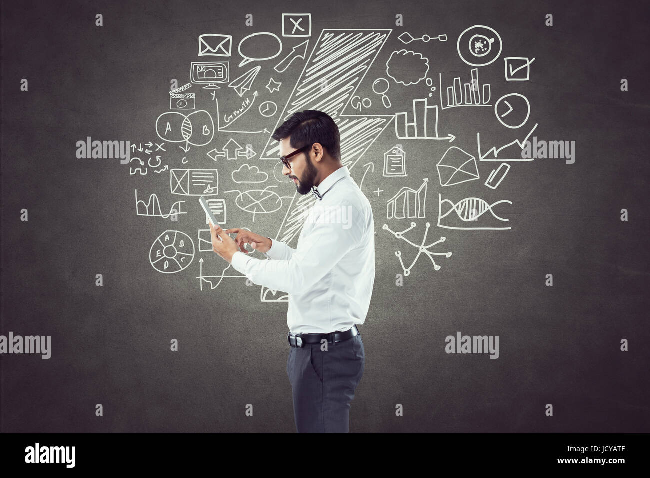 Businessman using digital tablet in front of blackboard with icons - Stock Image
