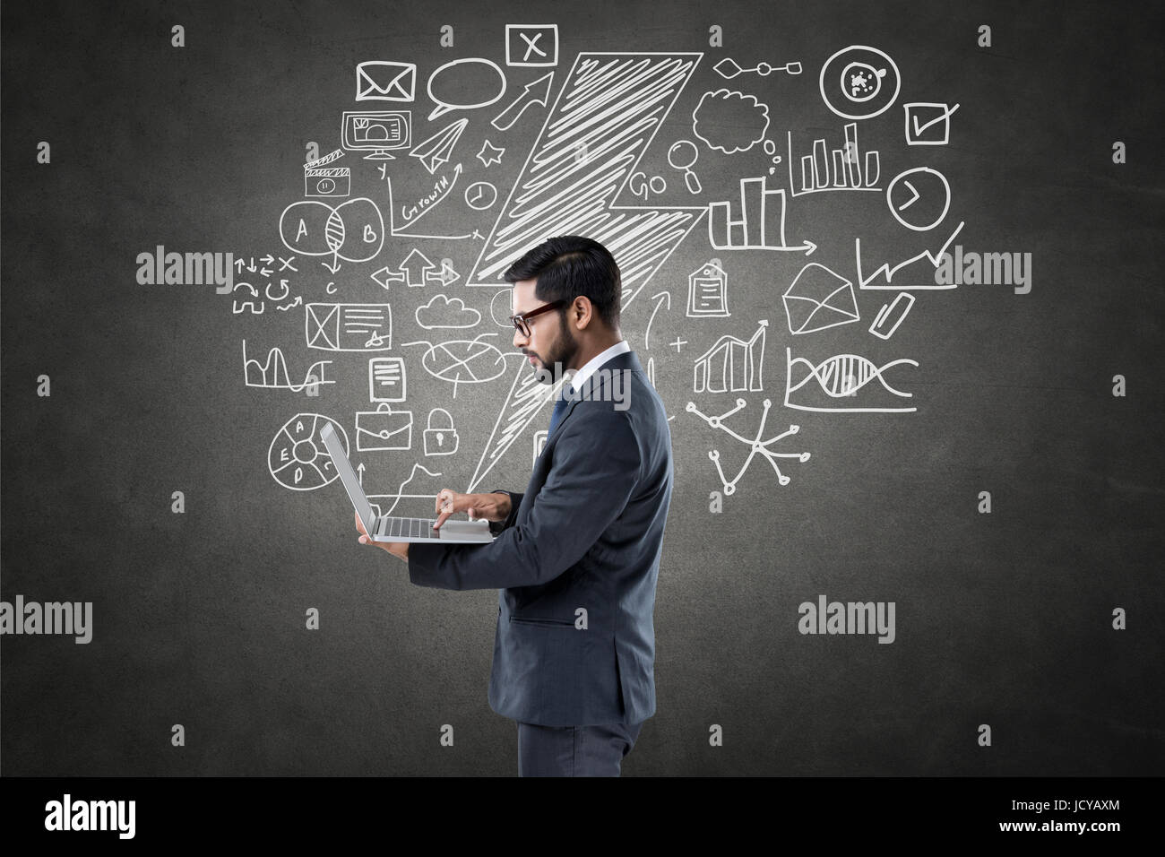 Businessman using laptop in front of blackboard with icons Stock Photo