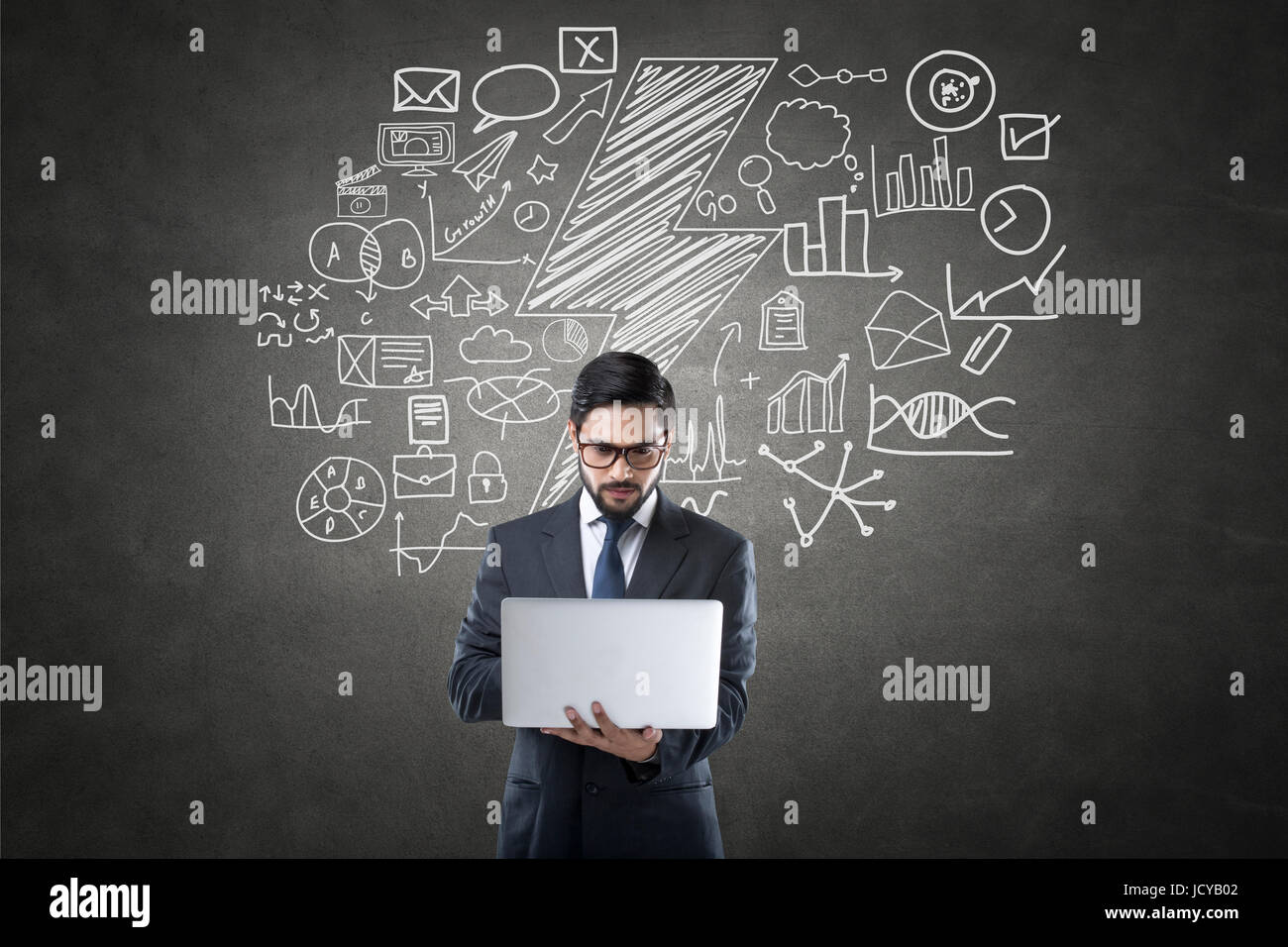Businessman using laptop in front of blackboard with icons - Stock Image