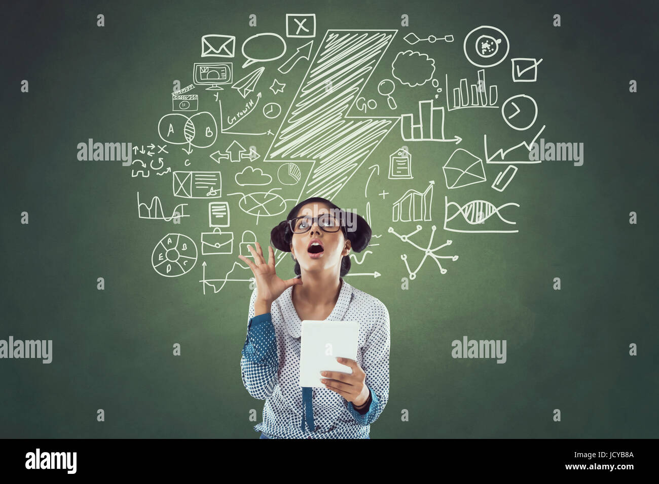 Businesswoman using digital tablet in front of blackboard with icons - Stock Image