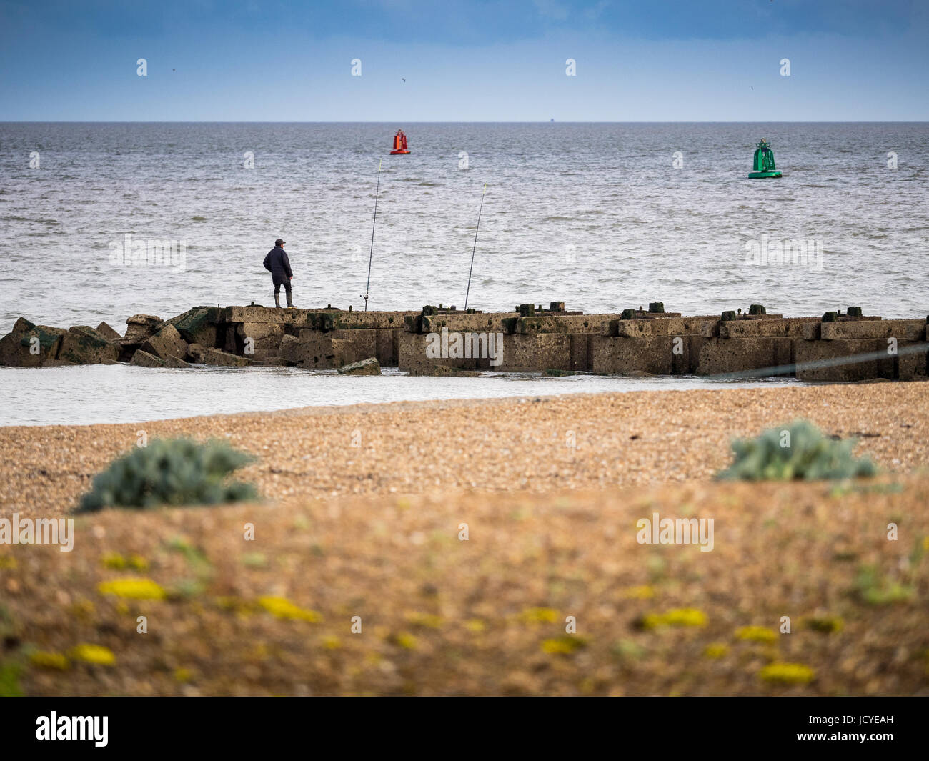 Sea fishing from a rock jetty in the small seaside town of Felixstowe, Suffolk, UK - Stock Image