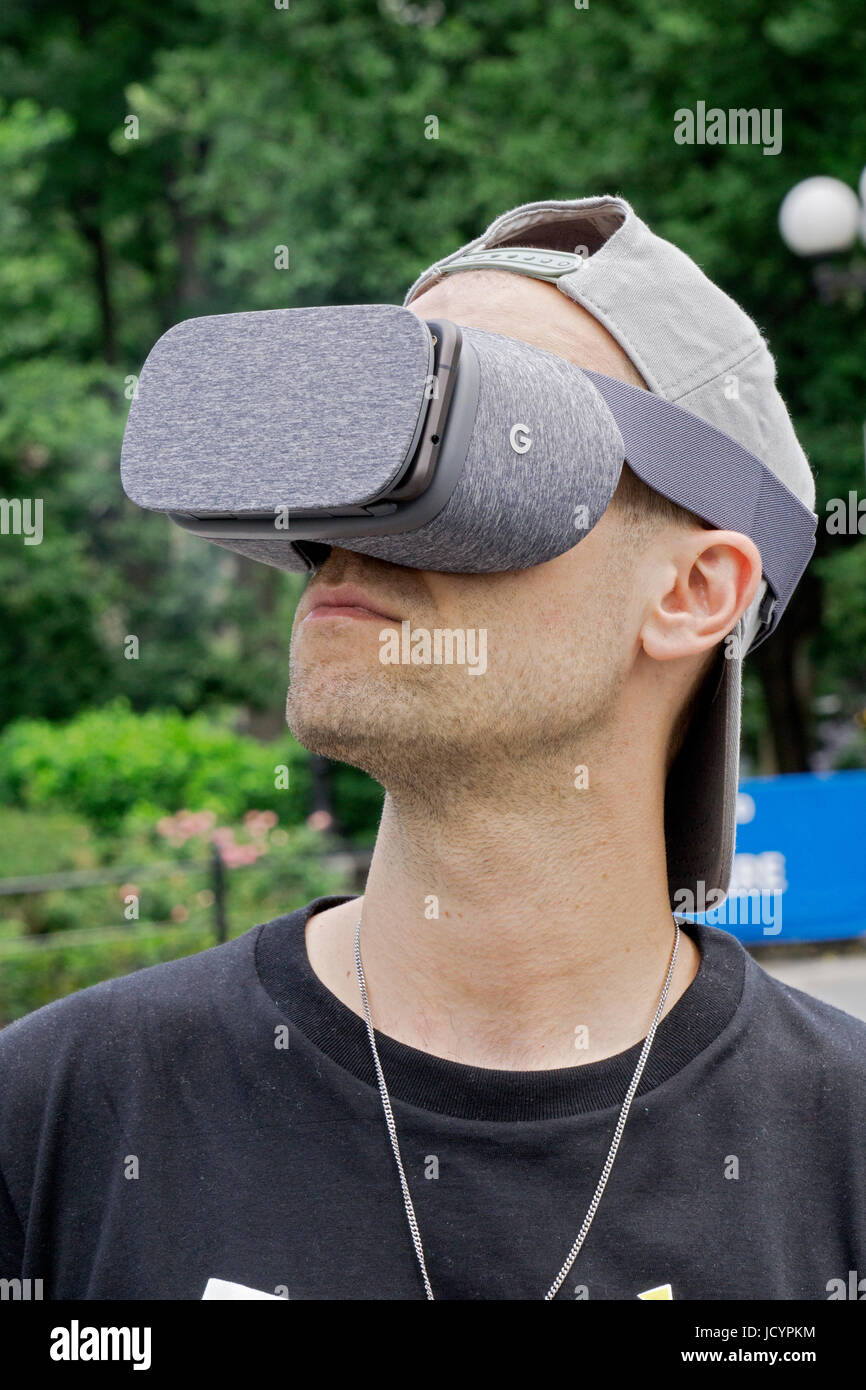 A young man in Union Square Park wearing a Google Daydream mobile virtual reality headset. - Stock Image